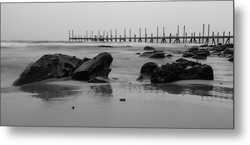 Black Rocks On Sandy Beach With Wooden Pier - Metal Print from Wallasso - The Wall Art Superstore