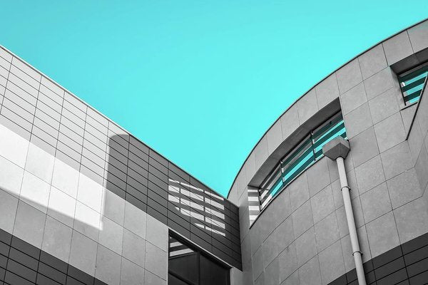 Grey Building With Bright Blue Sky - Art Print from Wallasso - The Wall Art Superstore