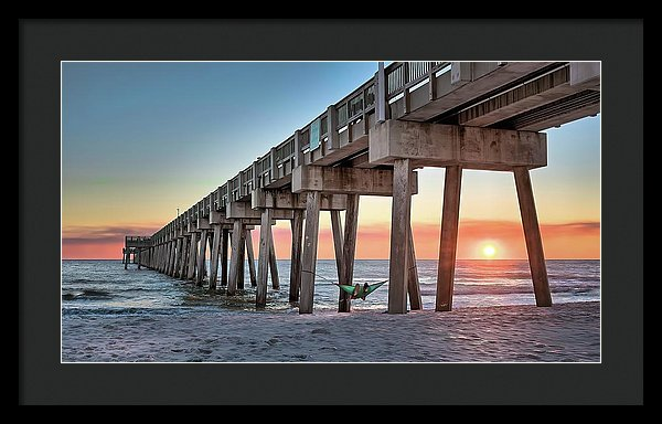People In Hammock Watching Sunset Under Pier - Framed Print from Wallasso - The Wall Art Superstore