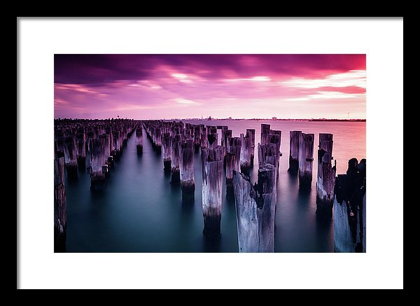 Wooden Poles In Water With Vibrant Pink Sky - Framed Print from Wallasso - The Wall Art Superstore