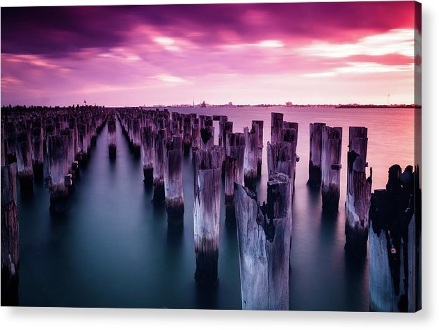 Wooden Poles In Water With Vibrant Pink Sky - Acrylic Print from Wallasso - The Wall Art Superstore