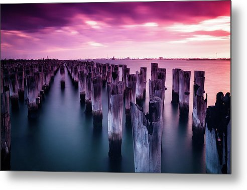 Wooden Poles In Water With Vibrant Pink Sky - Metal Print from Wallasso - The Wall Art Superstore