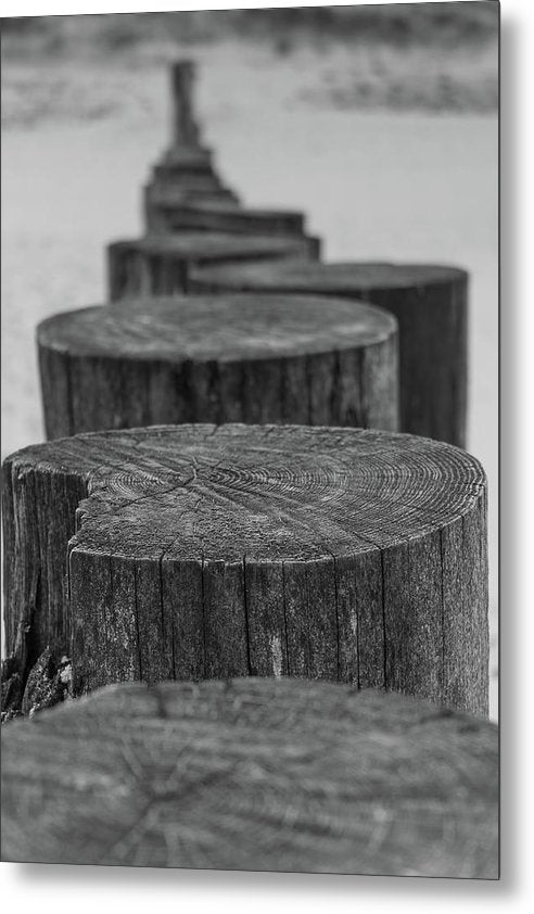 Wooden Posts On Sandy Beach - Metal Print from Wallasso - The Wall Art Superstore