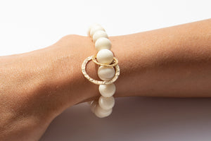 White Bone Beaded Bracelet With Two Solid 14k Yellow Gold Circle Charms Featured on Arm