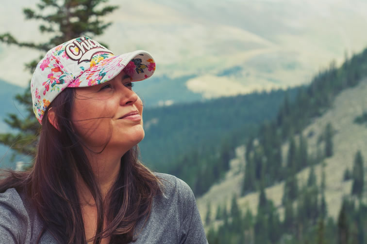 Woman hiking in the mountains and smiling feeling relaxed