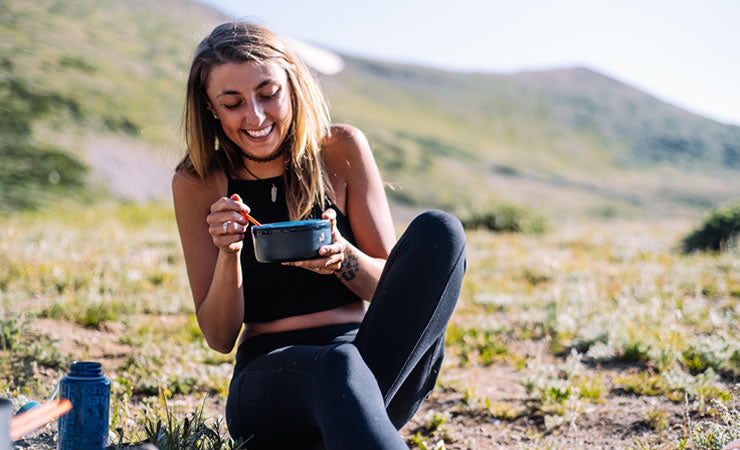 Young woman outside smiling and laughing after enjoying taking CBD treats orally