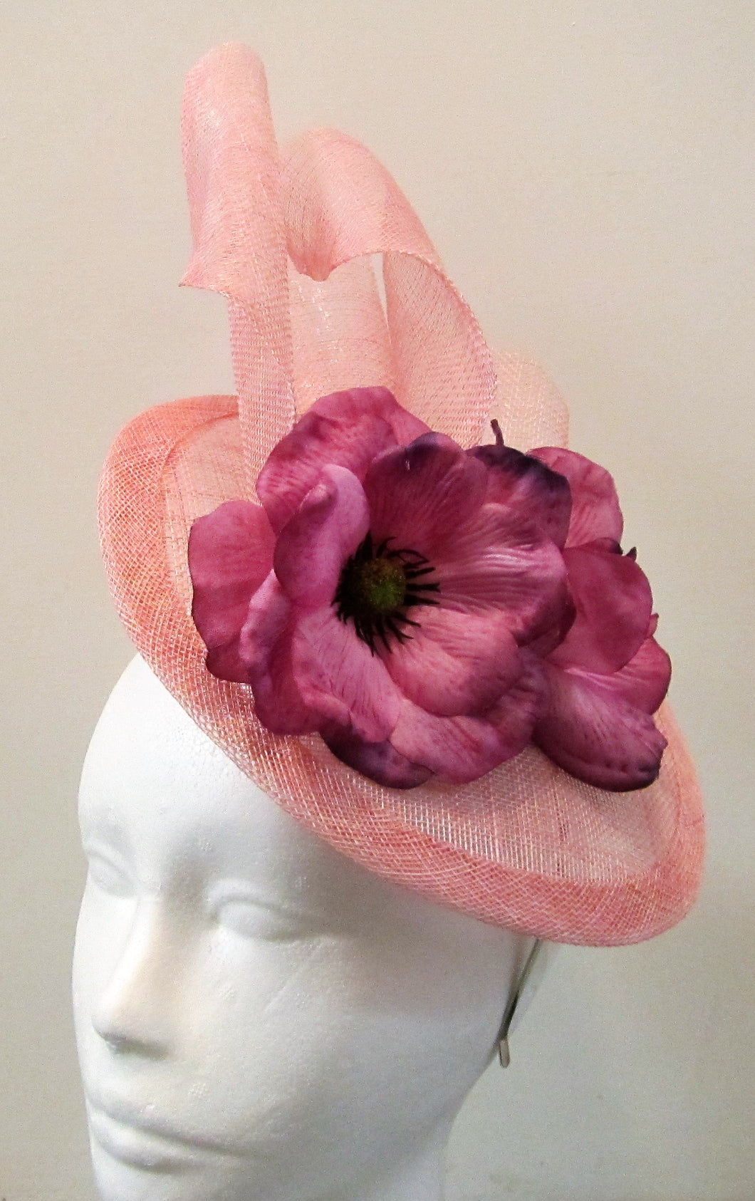 Handcrafted light pink disk with waves and purple flowers fascinator on a hair band