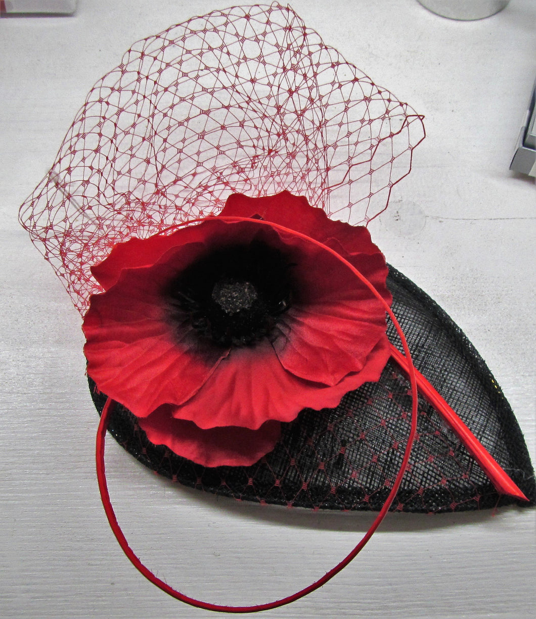 Handcrafted red and black poppy fascinator on a hair comb