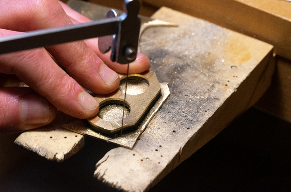 After the metal sides have been attached, cutting the excess side material off the base of the ring.