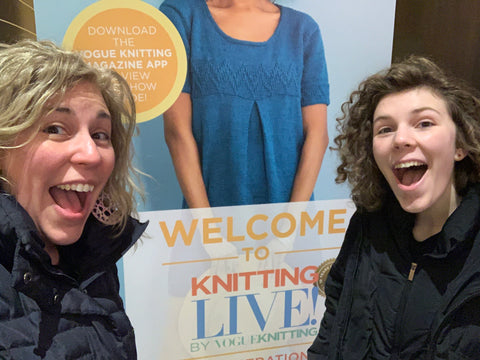 two women with excited faces stand in front of a sign for an event they are attending.  They can't wait for it to start!