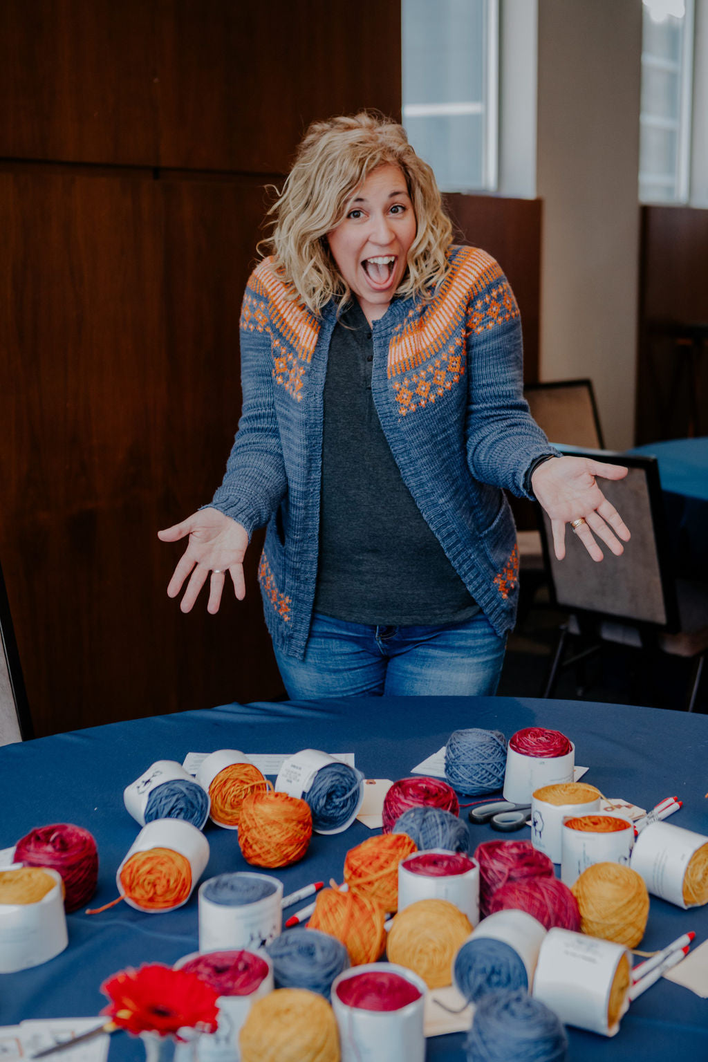 Jill smiles excitedly at the camera, outstretching her hands toward the viewer, as if to show them the yarn on the table before her.  The table is covered by a dark blue tablecloth and is covered in balls of yarn, ready to be knitted or crocheted.  The yarns are Yellow, Orange, Red, and Blue.  Jill wears jeans and a dark top, with a hand knitted sweater on top.  The sweater is blue with orange and pink color work on the yoke.