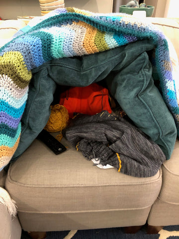 Pile of green throw pillows and a striped crocheted blanket surrounding a knitting project and orange knitting bag, on a beige couch cushion