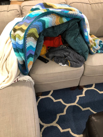 Yarn fortress made out of teal throw pillows and striped blankets, creating a little fort for Momma's knitting project on the beige couch