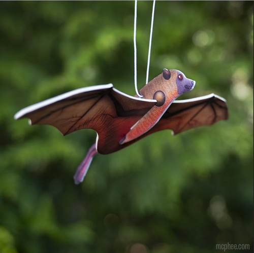 Bat-shaped paper air freshener with 3D wings. Item is hanging from a white string against a blurred, green leaf backdrop.