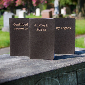 "Three pocket-sized notebooks, each with a different inscription in serif font - from left to right, ""deathbed requests,"" ""epitaph ideas,"" and ""my legacy."" The notebooks are taken on top a gravestone with a blurred cemetary image in the background."