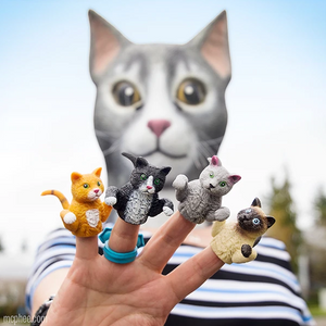 A human hand with a cat puppet on each finger - from left to right: orange tabby, tuxedo, grey, and siamese. The backdrop is the person displaying the puppets while wearing a grey rubber cat mask.