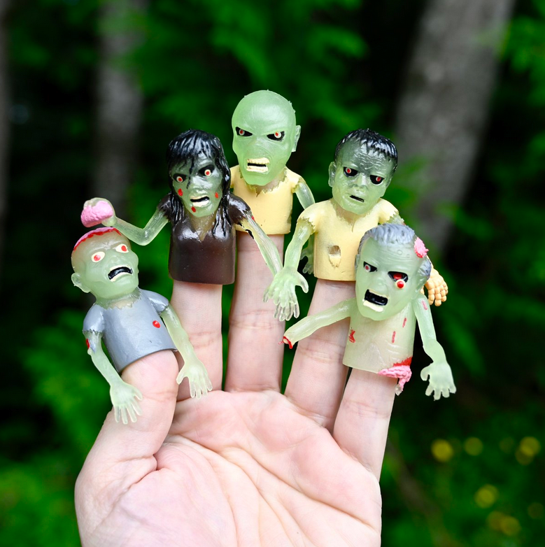 A human hand with five zombie finger puppets - from left to right: one with an exposed brain, one holding a brain, one that is bald and scowling, one with black hair, and one with a popped-out eye and exposed brain.