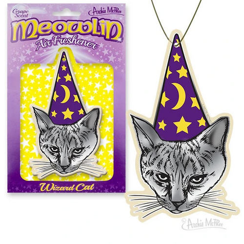A paper air freshener shaped like a grey cat wearing a purple cone hate with stars and a crescent moon. In the background, there is purple and yellow packaging reading