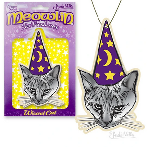 "A paper air freshener shaped like a grey cat wearing a purple cone hate with stars and a crescent moon. In the background, there is purple and yellow packaging reading ""Meowlin."""