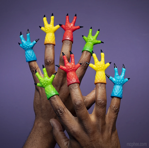 Two hands wearing one four-digit claw finger puppet on each finger. They are assorted colors including red, yellow, blue, and green.