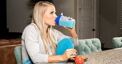 Woman sat down drinking BCAA's before workout