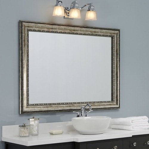 Wall mirror with an aged silver frame, above a wood vanity and surrounded by light blue walls.