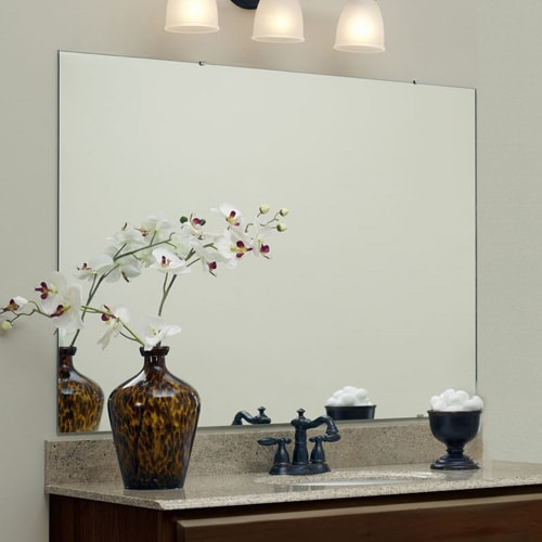 Large, wall mounted vanity mirror sits atop of a granite counter and backsplash.