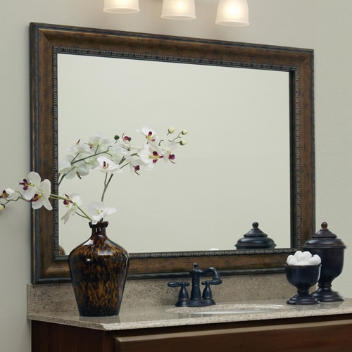 Large mirror with dark bronze colored frame, situated above the vanity.