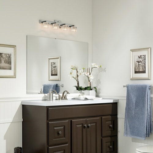 Transitional bathroom with light walls, wainscotting, white countertop, dark wood vanity and brushed silver accents and artwork.