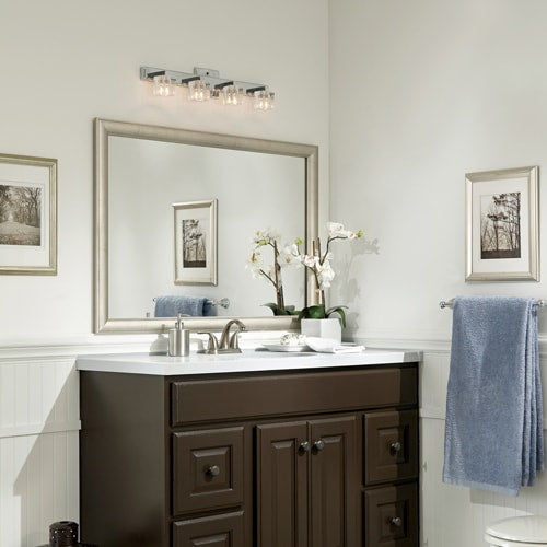 Bathroom featuring light walls, wainscotting, a dark painted vanity topped with white counter and accentuated with brushed silver hardware, artwork and brushed silver mirror frame.