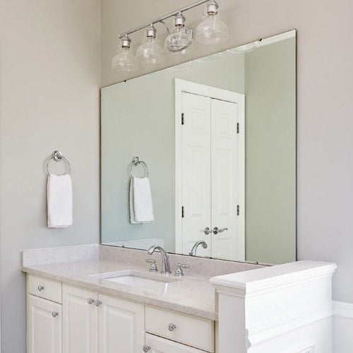 Newly remodeled bathroom with white vanity and updated lighting - but no frame on the mirror.