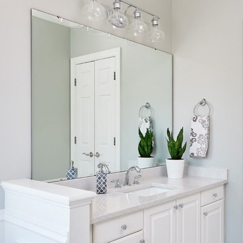 All white bathroom with silver faucet and lighting.