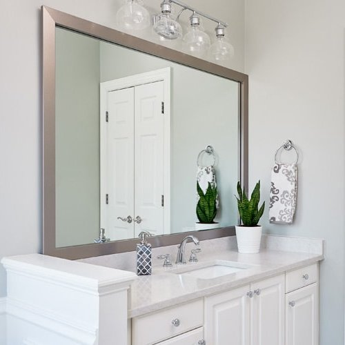 Modern bathroom features a silver mirror frame in Broadway Brushed Chrome and sits atop a white vanity and white counter.
