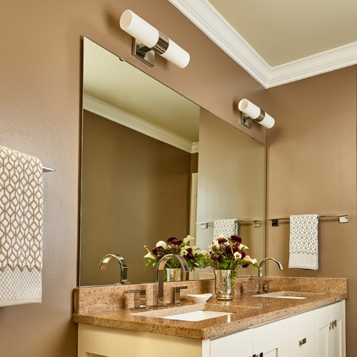 Modern bathroom with white vanity, taupe walls, taupe granite, silver hardware and no frame on mirror.
