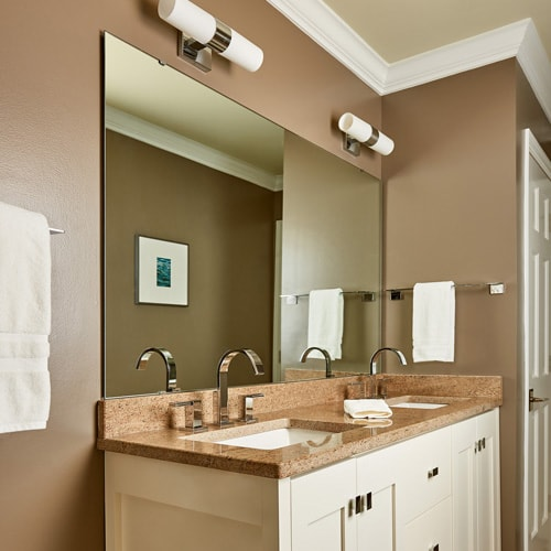 A modern bath with white vanity, taupe walls, granite counter and sleek silver lighting.