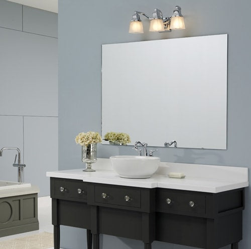 Transitional bath set in a blue painted bathroom with dark wood vanity, white counter and vessel sink.