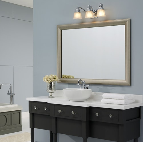 Transitional bath with blue walls, dark wood vanity, white countertop , vesssel sink and brushed silver frame on mirror complimenting silver faucet.