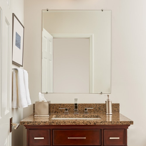 Transitional style cherry vanity with granite counter, silver faucet and unframed mirror.