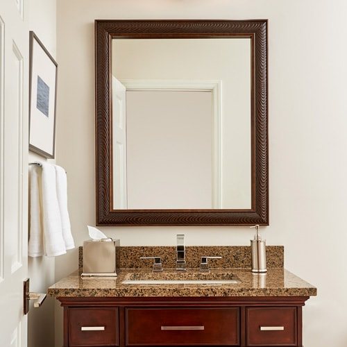 Mirror frame in Venetian Silver Wave matches the transitional style cherry vanity and is a contrast to the light walls.