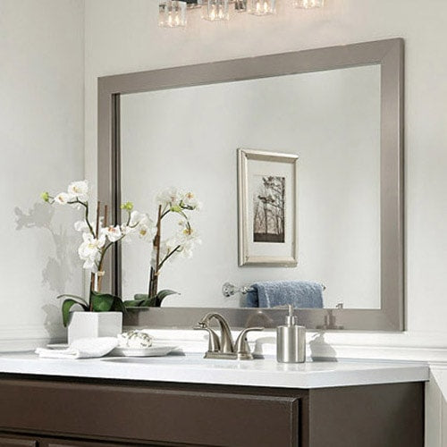 Bathroom with a brown painted cabinet, white walls, white counter, blue hand towel and a mirror framed in the sleek, silver frame style Broadway Brushed Chrome.