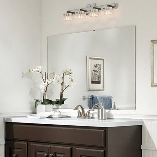Dark painted vanity and white countertop surrounded by white walls, wainscoting and an orchid.