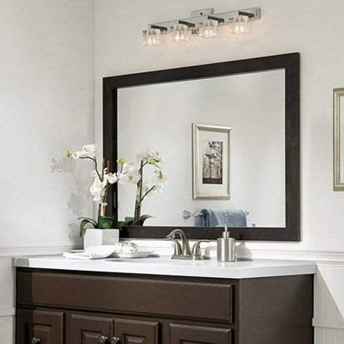 Dark brown painted vanity topped with a white countertop, and brushed silver accents in hardware, mirror frame and artwork.