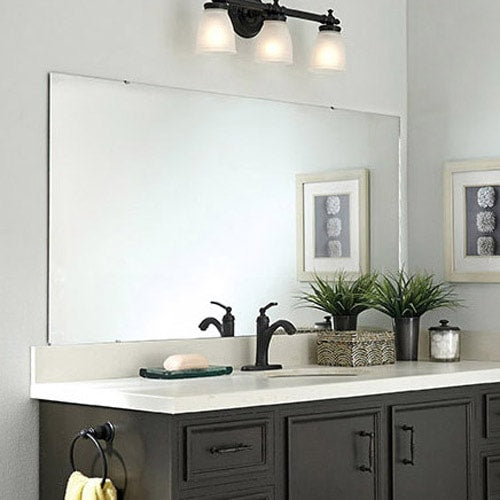 Transitional style dark wood vanity with oiled bronze hardware, white counter, light blue walls and unframed mirror.