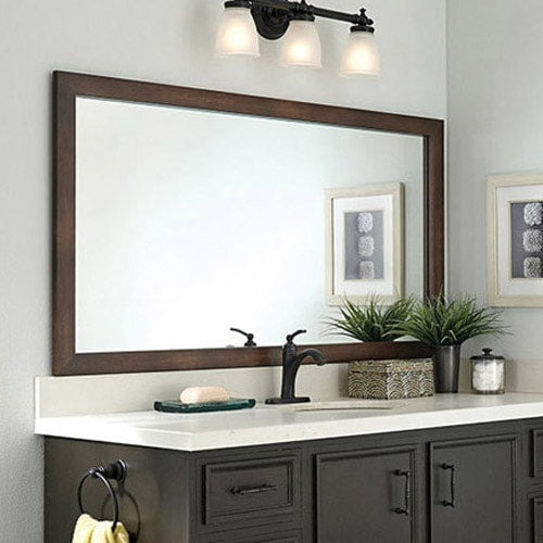 Transitional style dark wood vanity with oiled bronze hardware, white counter, light blue walls and a dark wood mirror frame in the Cherokee Mocha Walnut style.