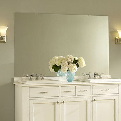Soft, feminine bath with a light green walls, white vanity, counter and hydrangeas.