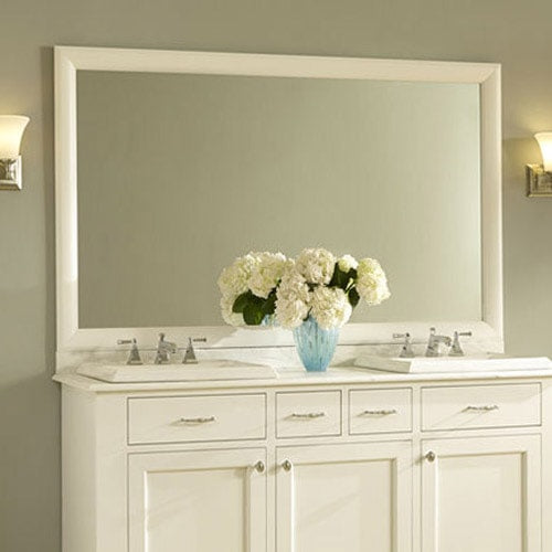 Pretty white vanity and counter, topped with a white mirror frame in Pemaquid Porcelean White set in a light green bathroom.
