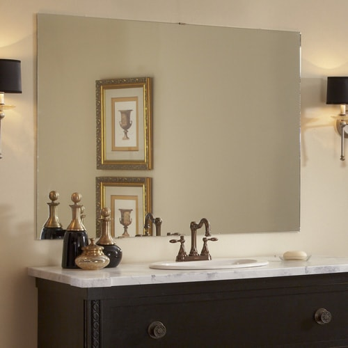 Dark wood traditional bathroom vanity topped with marble counter and oiled bronze faucet and a plate glass wall mirror set in a green/grey bathroom with oiled bronze hardware and lighting.