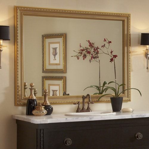This traditional dark wood bathroom showcases the Providence Gold mirror frame atop the wall-mounted mirror, complimenting theoiled bronze hardware and lighting in the bath.
