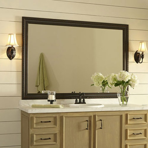 The Providence mirror frame in Oiled Bronze outlines the plate glass mirror, making it the focal point of a neutral bathroom with white shiplap walls and a light wood vanity.