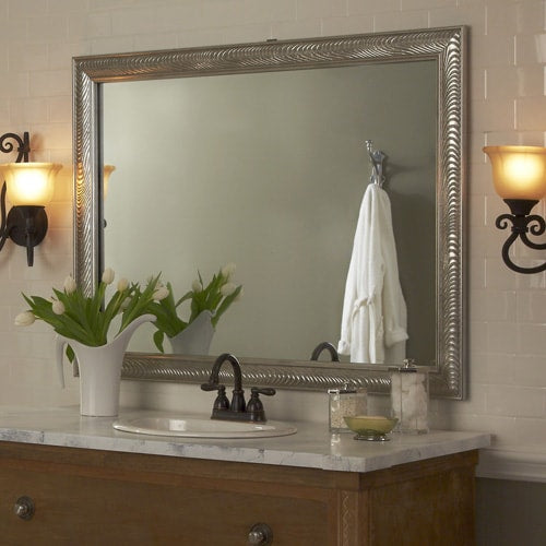 Venetian Silver Wave mirror frame adornes the vanity mirror, while the wall is covered in white subway tile, the counter is marble and the vanity is wood.